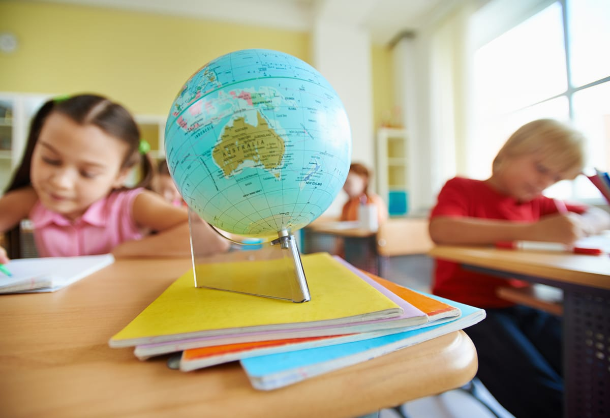 Globe on stack of copybooks on background of schoolchildren drawing at lesson